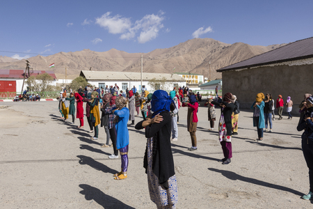 Murghab, Tajikistan, August 23 2018: Kyrgyz girls and young women are practicing a dance on the playground of a school in Murghab. Against the strong sunlight they have protected their faces with scarves.
