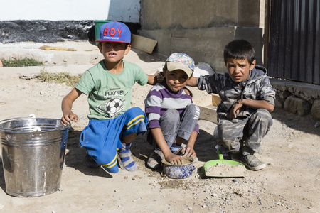 Murghab, Tajikistan, August 23 2018: Three Tajik children pose in front of their home in Murghab along the route of the Pamir Highway Editorial