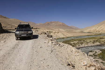 Langarl, Tajikistan, August 23 2018: Off-road car is waiting on the Pamir Highway on the Pamir River. On the left of the river is Tajikistan and on the right Afghanistan