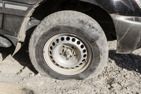Langar, Tajikistan, August 23 2018: Flat tire on the Pamir Highway near Langar in the border area between Tajikistan and Afghanistan Editorial