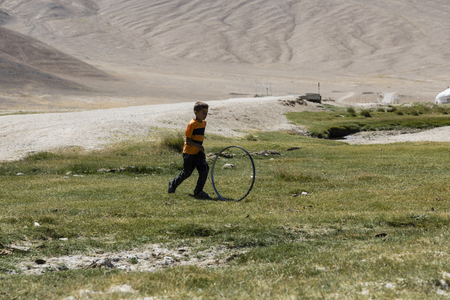 Bulunkul, Tajikistan, August 23 2018: A child in the village of Bulunkul in the Pamir mountains plays with an old bicycle rim