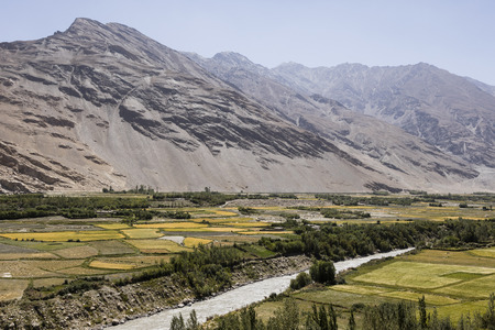 Fertile Wakhan Valley with Panj river near Vrang in Tajikistan. The mountains in the background are the Hindu Kush in Afghanistan Reklamní fotografie - 115756108