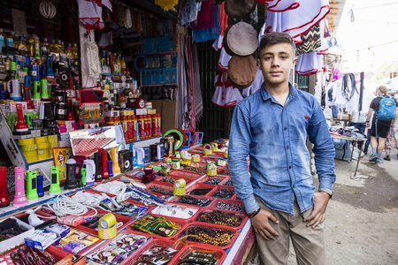 Khorog, Tajikistan August 25 2018: Handsome boy is standing in front of his stall, waiting for buyer of his wares, Khorog, Tajikistan