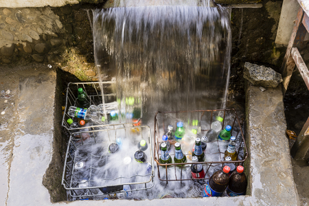 Khorog, Tajikistan August 25 2018: At the roadside on the Pamir Highway in Tajikistan drinks are cooled under a small waterfall