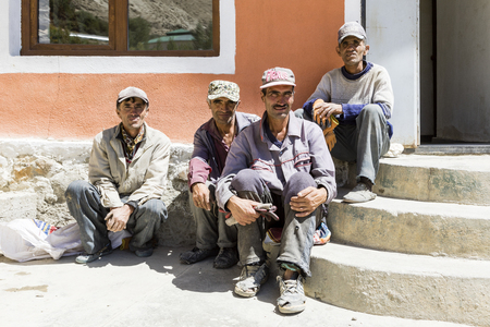 Vrang, Tajikistan August 24 2018: Four older men are sitting on the stairs in front of the Bibi Fatima hot springs in Wakhan valley in Tajikistan Editorial