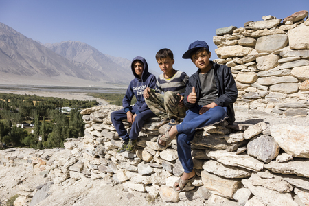 Vrang, Tajikistan August 24 2018: Three boys are sitting in Vrang on a Buddhist temple in the Wakhan valley in Tajikistan Editorial