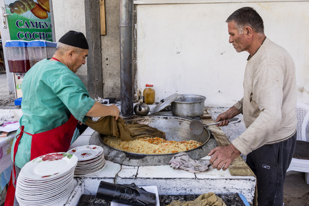 Khorog, Tajikistan August 25 2018: Two sellers are cooking a rice dish in a big pancake at the market in Khorog in Tajikistan