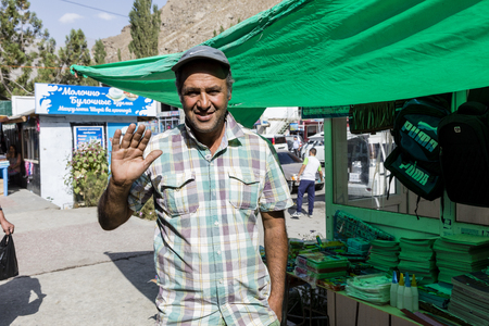 Khorog, Tajikistan August 25 2018: Male seller in front of his stall at the market of Khorog in Tajikistan