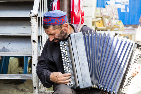 Khorog, Tajikistan, August 20 2018: An old musician plays on the bazaar in Khorog on his accordion Editorial