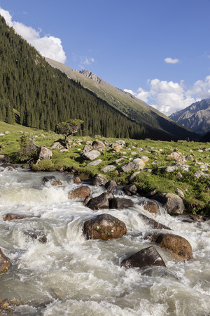 Valley of Altyn-Arashan in the late afternoon with a creek in the foreground in Kyrgyzstan