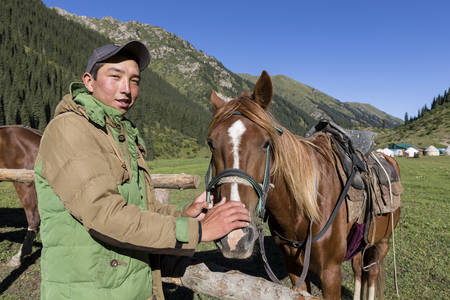 Altyn-Arashan, Kyrgyzstan, August 14 2018: A young Kyrgyz lovingly strokes a horse in the valley of Altyn-Arashan in Kyrgyzstan