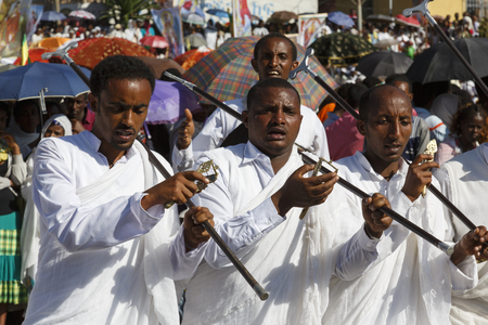 Gonder, Ethiopia, February 18 2015: Men dressed in traditional attire with pilgrim rod celebrate the Timkat festival, the important Ethiopian Orthodox celebration of Epiphany Imagens - 120453726
