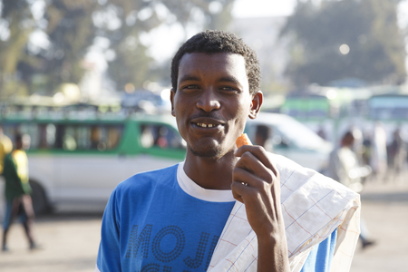 Bahir Dar, Ethiopia, February 15 2015: A young Ethiopian stands in the backlight and eats a carrot Editorial