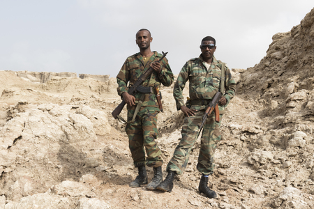 Danakil, Ethiopia, January 22 2015: Two soldiers posing proudly with their guns in the salt mountains of the Danakil desert