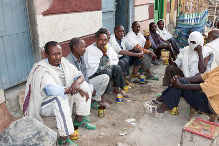 Hamd Ela, Ethiopia, February 23 2015: Ethiopian men sit outside in the street talking and drinking a local drink from old tin cans