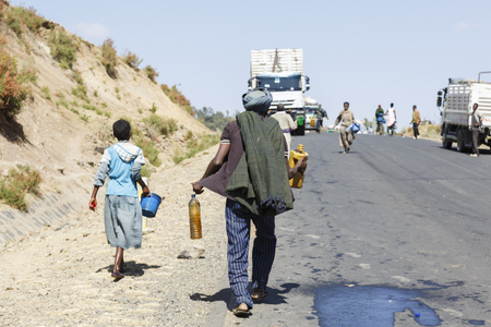 Addis Abeba, Ethiopia, January 15 2015: Locals fill up their canisters with diesel that spills out of an overturned tanker truck