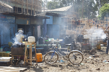 Bahir Dar, Ethiopia, February 14 2015: Market scene in Bahir Dar with smoking hearths, a bicycle in the foreground and a carpentry in the background