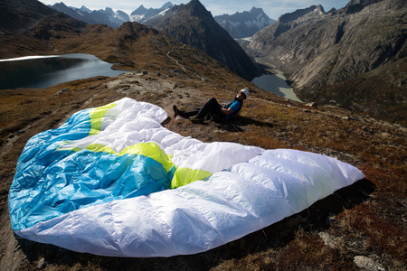 Paraglider Pilot sits with his paraglider on the ground and recovers after ground handling