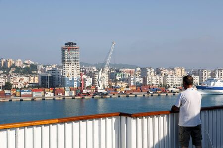 Durres, Albania, July 4 2019: Passenger stands on deck and looks at Durres in Albania during the docking maneuver