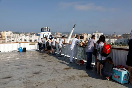 Durres, Albania, July 4 2019: Passengers watch the ferry landing in Durres harbor on the deck Banco de Imagens - 138488095