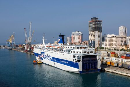 Durres, Albania, July 4 2019: Passenger ferry waits for departure at the pier in Durres. In the background you can see the modern city with the high-rise buildings