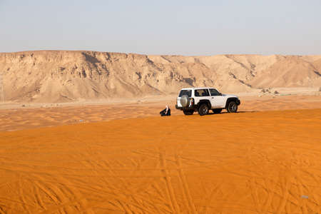 Riyadh, Saudi Arabia, February 15 2020: A Saudi has parked his car on a sand dune. He is now sitting in the sand and enjoys the view of the red sand dunes south of Riyadh