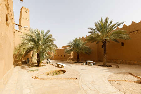 Public place with palm trees and renovated houses in the traditional village of Shaqra in Saudi Arabia. Shaqra is a traditional restored village made of clay bricks