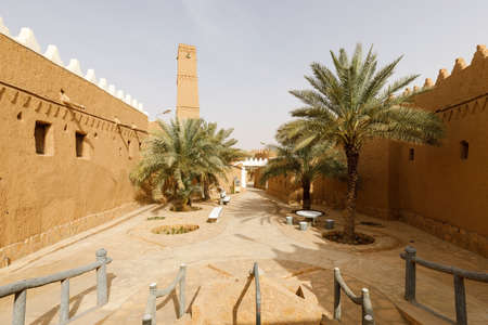Alley with palm trees and renovated houses in the traditional village of Shaqra in Saudi Arabia. Shaqra is a traditional restored village made of clay bricks Standard-Bild