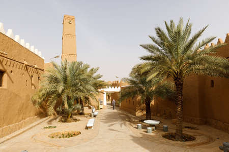 Shaqra, Saudi Arabia, February 16 2020: Alley with palm trees and renovated houses in the traditional village of Shaqra in Saudi Arabia. Shaqra is a traditional restored village made of clay bricks Editorial