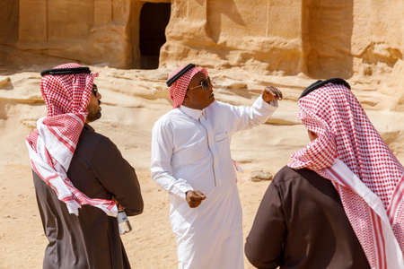 Al Ula, Saudi Arabia, February 19 2020: Two Saudi tourists with a guide in Jabal Al Banat, one of the largest clusters of tombs in Hegra that have skillfully carved facades, KSA