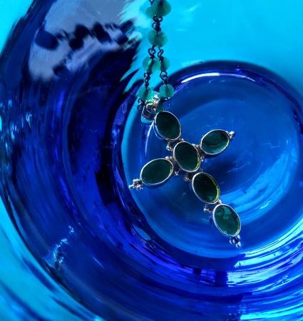 cross jewel pendant in a blue glass beaker