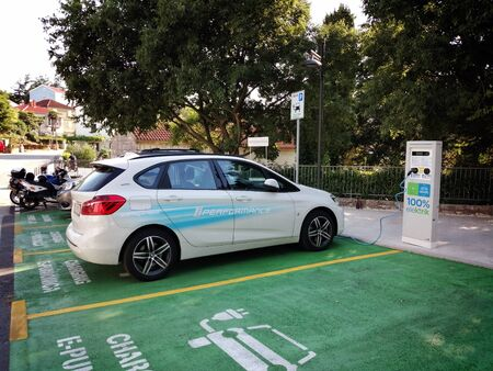Electric car charging at a charging station Archivio Fotografico - 127776165