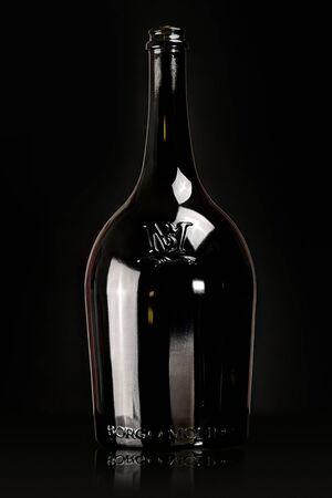 Black glass bottle of wine on the black background, still life