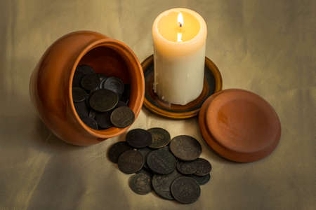 kopek: The hoard of copper coins of the Russian Empire in a clay pot. A burning candle.