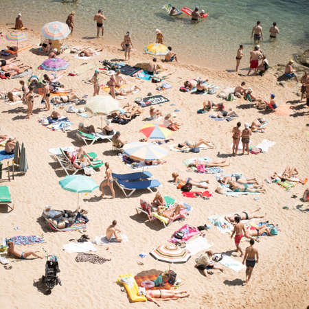 sun umbrellas: People and sun umbrellas on the beach