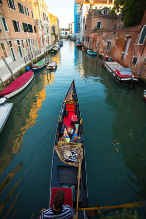 Venetian gondolier punting gondola through green canal waters of Venice, Italy photo for you Stock Photo