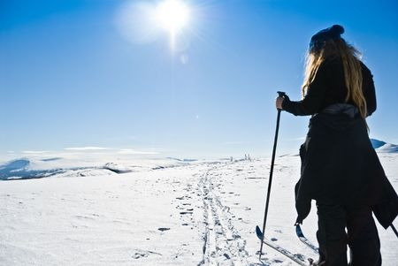 cuntry: A single young lady (with dreads) cross cuntry skiing towards a ski camp. Beautiful winter day. Picture taken in Oppdal, Norway.