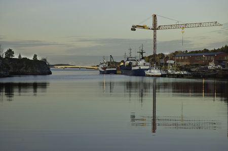 a small dock with some ship. a big crane, and the evening sun. photo