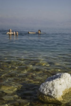 two people taking a swim in the dead sea. persons out of focus, focus on a rock filled with salt crystalls photo