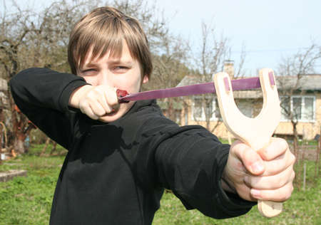 playful behaviour: Young boy with catapult in a garden Stock Photo