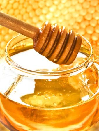 hive: Honey dipper en el nido de abeja de miel de abeja bocado de fondo en frasco de vidrio y cera de los panales