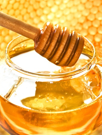 Honey dipper on the bee honeycomb background  Honey tidbit in glass jar and honeycombs wax