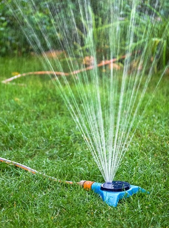 lawn sprinkler: Watering garden equipment  Irrigation system - technique of watering in the garden  Lawn sprinkler spraying water over green grass
