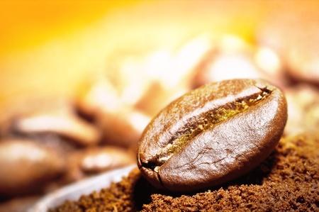 capuchinos: Granos de café árabe en el primer plano del haz de luz dorada de los granos de café en el montón de café tostado