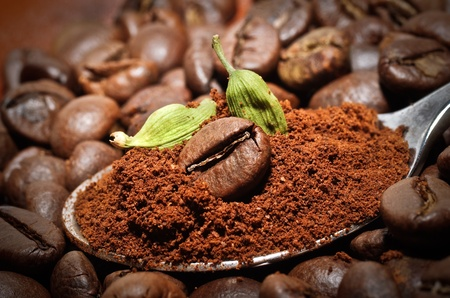 Arabic coffee beans with green cardamom - traditional oriental drink  Closeup of coffee beans at roasted coffee heap  photo
