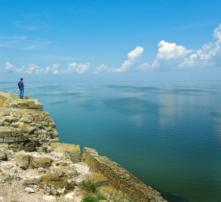 shore line: Horizon line above the smooth surface of the water with blue sky and clouds over the ocean  Seascape of the calm weather - man on the high coast looking of the horizon line, waiting for the ship  Stock Photo