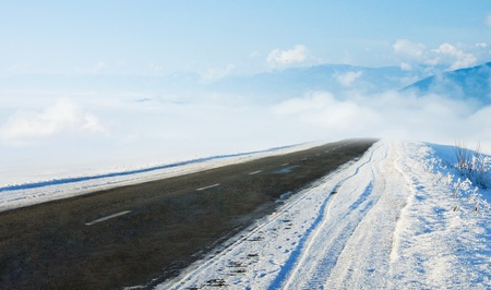 sleet: Snow covered road in winter with mountains in the distance  Travel background with mountains and auto track  Snowy highway with cloudy landscape