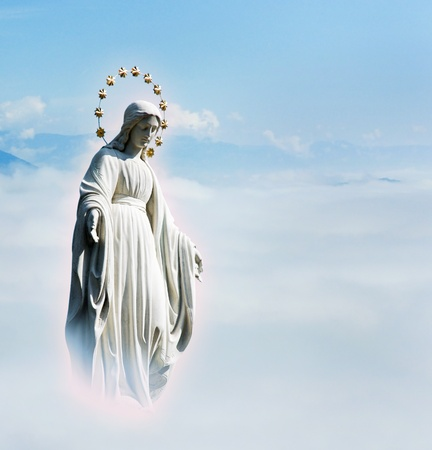 Blessed Virgin Mary at the sky background Mother Mary statue Holy phenomenon of the Holy Maria in the halo of glow in the sky above the clouds