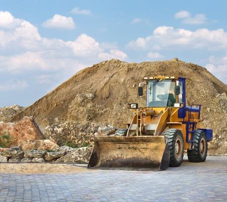 Bulldozer amarillo en una obra de construcci�n trabajando en un mont�n de grava. Construcci�n de escena con una excavadora peque�a. Foto de archivo - 13362426