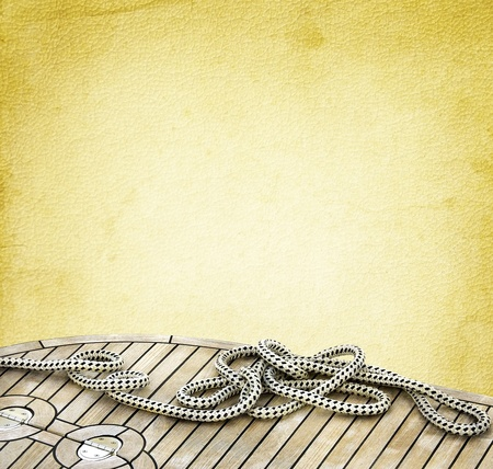 Ship rope on the old paper background  Sailboat ropes and wooden deck of the vintage textured background  Marine design frame with elements of yachting  photo